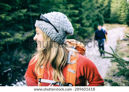 Man and woman hikers walking with backpacks on trail in green forest mountains. Young couple camping and trekking on country road, healthy lifestyle in beautiful nature, Tatra Mountains, Poland. - stock photo