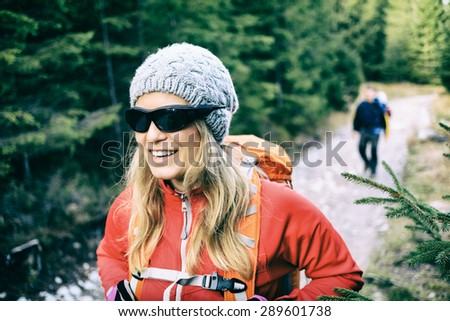 Man and woman hikers walking with backpacks on trail in green forest mountains. Young couple trekking on country road, healthy lifestyle in beautiful inspirational landscape, Tatra Mountains, Poland. - stock photo
