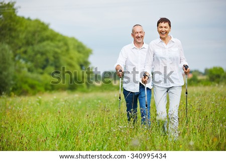 Man and woman hiking in summer over a meadow with walking sticks - stock photo