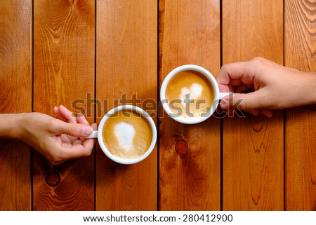 Man and woman holding a cup of coffee - stock photo