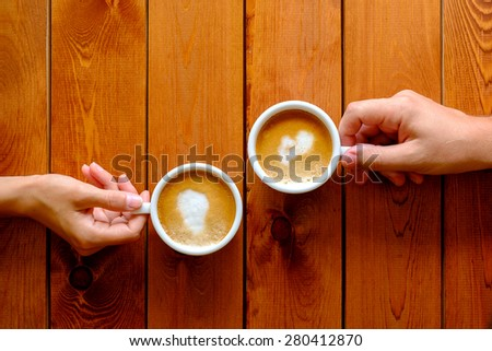 Man and woman holding a cup of coffee in the cafe - stock photo