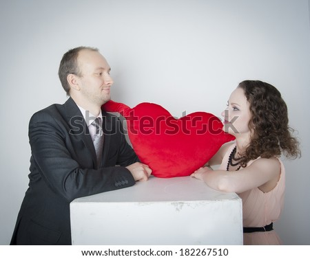 man and woman holding a red heart