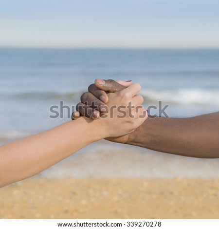 Man and woman holding each other s hand, symbol of love and diversity - stock photo