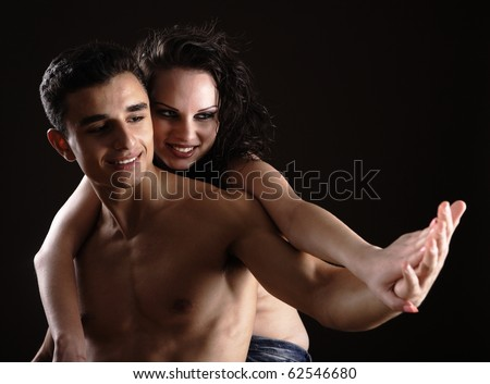 Man and woman holding each other shirtless isolated on black