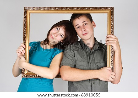 man and woman holding gold decorative frame and standing inside it - stock photo