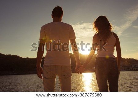 Man and woman holding hands at he beach and watching sunset - stock photo