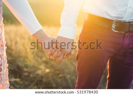Man and woman holding hands. Close-up.