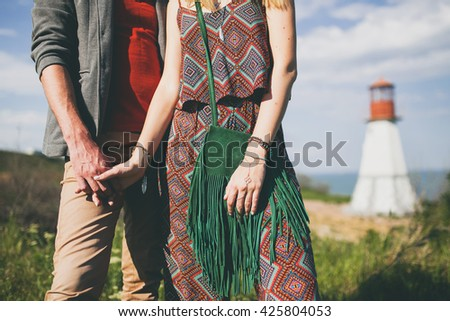 man and woman holding hands, hipster style, vintage 70's outfit, boho, indie trend, printed overall, green suede bag with fringe, lighthouse on background, nature, summer, stylish accessories