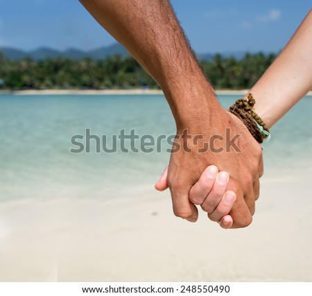 man and woman holding hands on the beach close-up