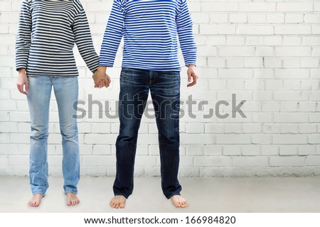 Man and woman holding hands together against white brick wall with copy space. Young couple wearing marine sailor uniform holding hands illustrating love and friendship - stock photo