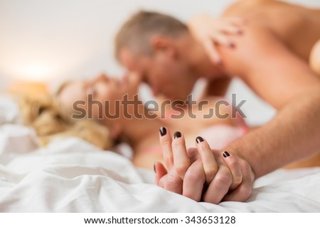 Man and woman holding hands while making love  - stock photo