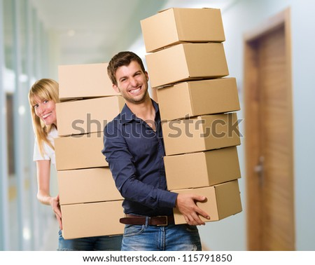 Man And Woman Holding Stack Of Cardboard, Indoor - stock photo