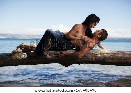 Man and woman hugging on the beach - stock photo