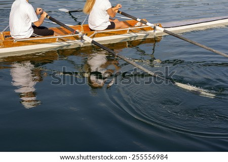 Man and woman in a boat, paddles on the tranquil lake - stock photo