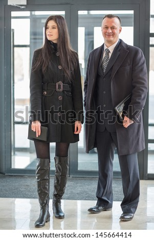 Man and woman in a coat stand near the glass door