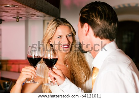 Man and woman in a hotel bar in the evening having glasses of red wine and a little flirt - stock photo