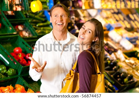 Man and woman in a supermarket at the vegetable shelf shopping for groceries, he is tossing a bell pepper and seems to be full of joy - stock photo
