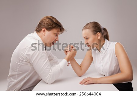 Man and woman in arm wrestling gesture on working table during meeting. Isolated over grey background. - stock photo
