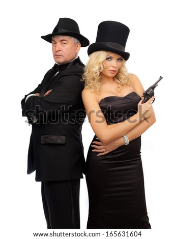 Man and woman in elegant suits and hats with a revolver. - stock photo