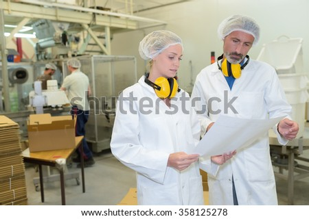 Man and woman in factory holding paperwork - stock photo