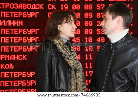 Man and woman in leather jacket standing in profile and look to each other in eyes on background of flight timetable - stock photo