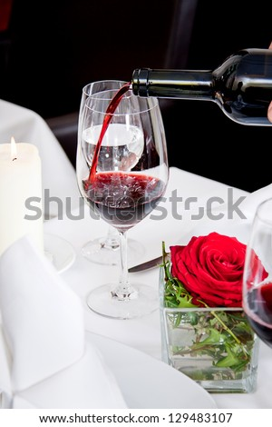 man and woman in restaurant for dinner drinking red wine and smiling