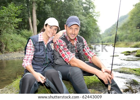 Man and woman in river fly fishing - stock photo