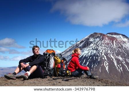 man and woman in sport clothing sitting in front of Tongariro volcano - Tongariro alpine crossing,  New Zealand - stock photo
