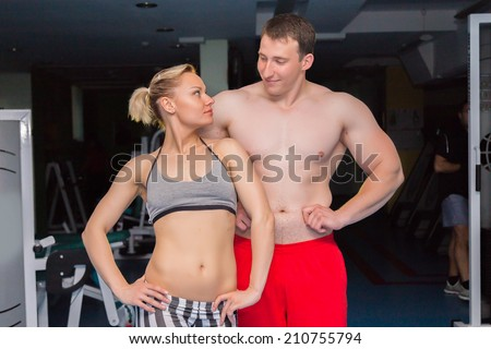 Man and woman in the gym. Fitness, sport, training, gym and lifestyle concept - two smiling people standing in the gym. The idea of article about sport and fitness.