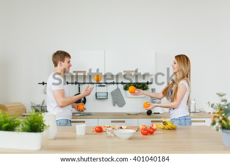 man and woman in the kitchen juggling oranges products. Playing and laughing - happy. Happy family life. Morning couples. - stock photo