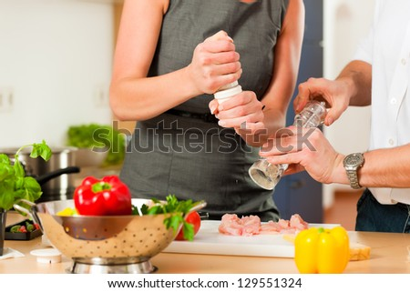 Man and woman in the kitchen - they preparing the vegetables and salad for dinner or lunch