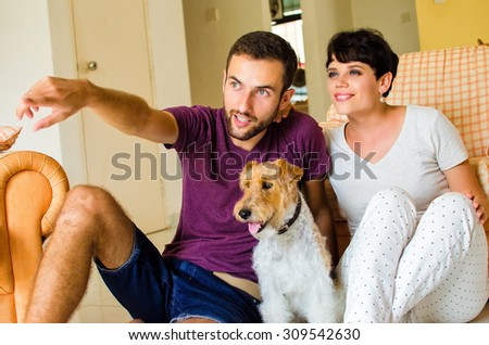 Man and woman in they house playing with the dog - stock photo