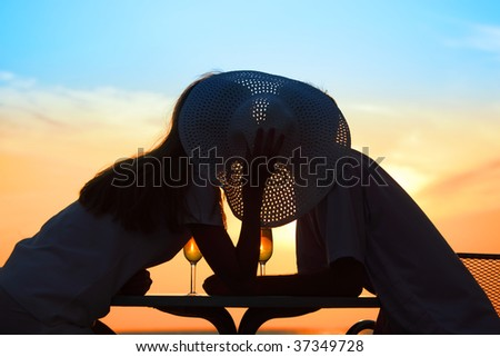 man and  woman kiss behind hat on sunset outside - stock photo
