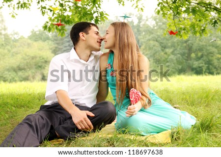 Man and woman kissing under a tree - stock photo