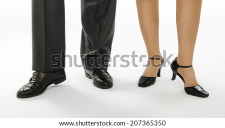 Man and woman legs dancing in crocodile shoes on white background - stock photo