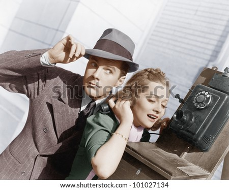 Man and woman listening on an outside telephone - stock photo