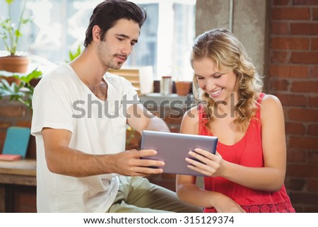 Man and woman looking at digital tablet in creative office