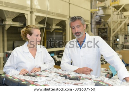 Man and woman looking at packages in factory - stock photo
