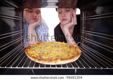 man and woman looks in a oven to their baking pizza - stock photo