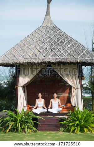 Man and woman meditating in hut - stock photo