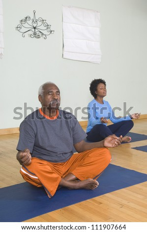 Man and woman meditating in lotus position - stock photo