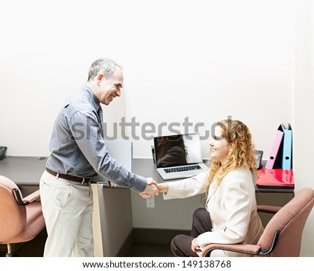 Man and woman meeting in office shaking hands - stock photo
