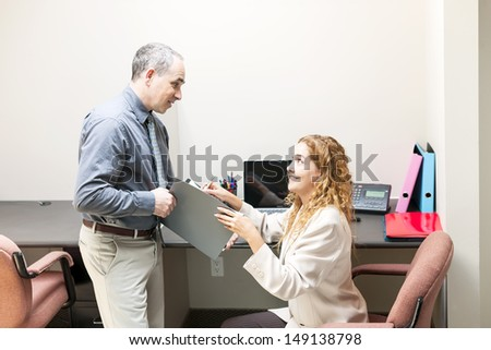 Man and woman meeting to discuss paperwork in office - stock photo