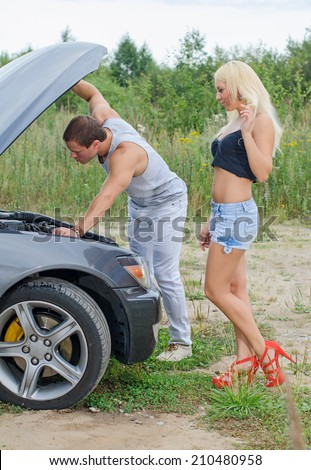 Man and woman near the broken car. - stock photo