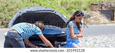 Man and woman near their broken car - stock photo