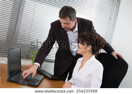 Man and woman, office workers in front of desktop computer - stock photo