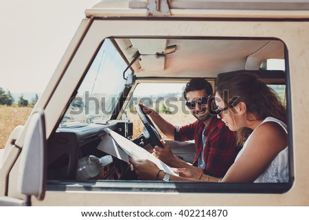 Man and woman on a road trip and reading a map together while seated inside their car. Happy young couple going on road trip. - stock photo