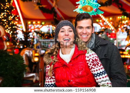 Man and woman or  a couple  or friends during advent season or holiday in front of a carousel or merry-go-round on the Christmas or Xmas market - stock photo
