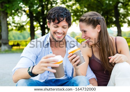 Man and woman or young couple drinking coffee and sitting in city park in summer on stairs - stock photo