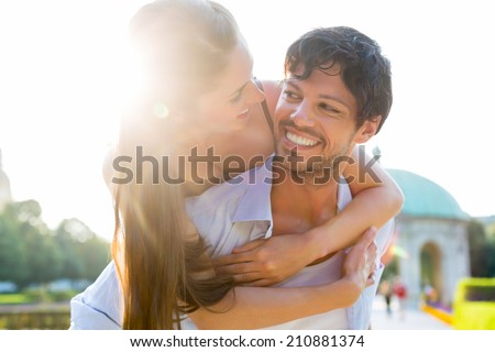 Man and woman or young couple making trip as tourists in park carrying each other piggyback